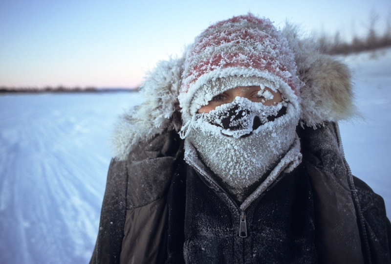 someone freezing cold, with face covered in snow and snow in the background